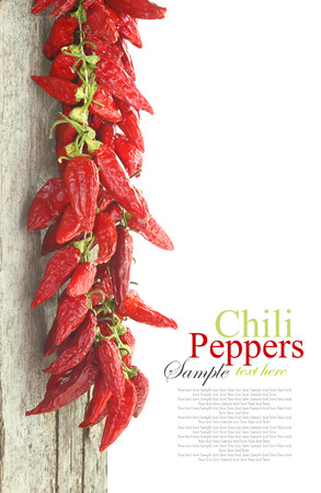 Red hot chili peppers hanging on wood, isolated on white photo