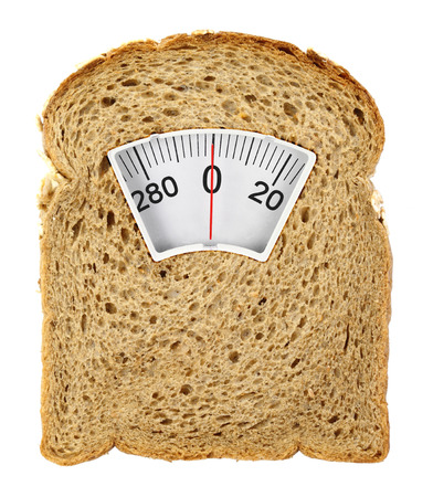 wholesome: Wholesome slice of bread as weighing scale isolated on white