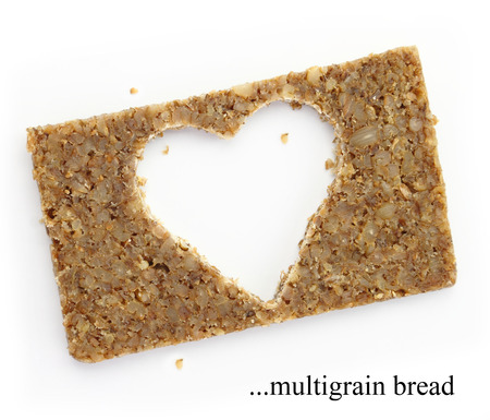 Multigrain slice of bread with copy space in shape of heart, isolated on white