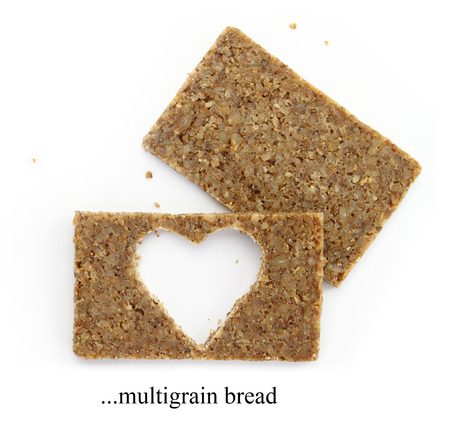Two multigrain slices of bread with cut out shape of heart, isolated on white Stock Photo - 22414743