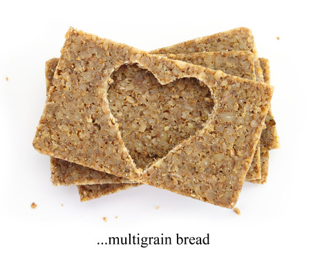 Stack of multigrain slices of bread, with cut out shape of heart, isolated on white photo