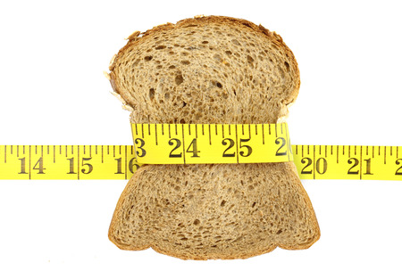 Wholesome slice of bread with measuring tape isolated on white Stock Photo - 22414745