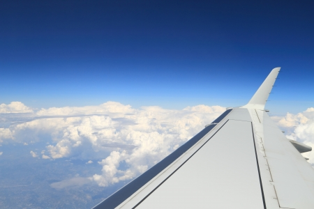 troposphere: Blue horizon and huge clouds, aerial shot from airplane, with wing visible