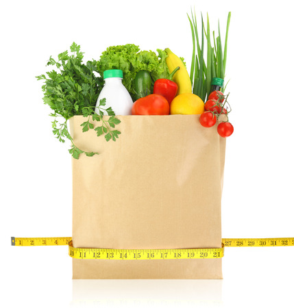 Fresh groceries in a paper bag with measuring tape photo