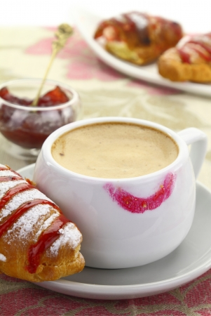 1874. Cup of coffee with lipstick mark and croissant with strawberry jam photo