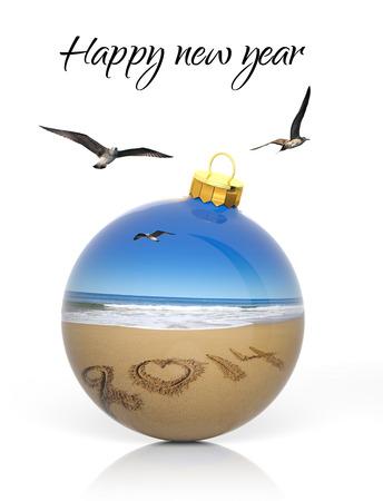Christmas ball with 2014 written on sandy beach  photo