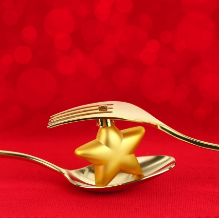 Christmas golden cutlery with ornament on red background photo