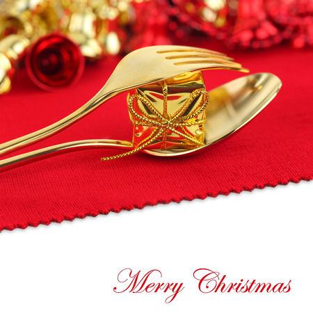 christmas catering: Christmas golden cutlery with ornament on red background
