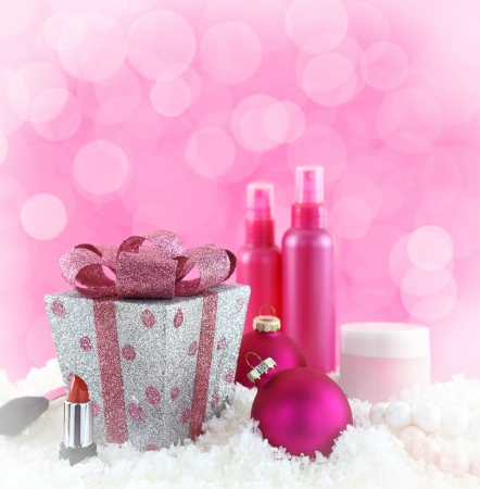beauty care: Christmas presents, beauty products with snow and pink background