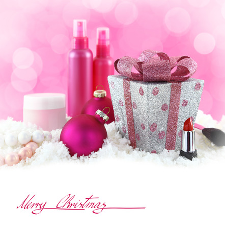 Christmas presents, beauty products with snow and pink background photo