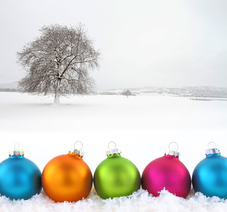 Colorful Christmas balls with snowfield as background photo