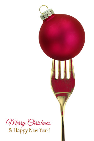 christmas catering: Golden fork with Christmas ball isolated on white background