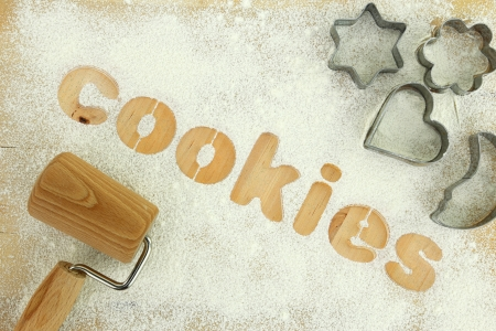 Stencil word cookies made with flour on wooden table photo