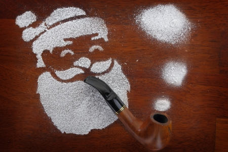 Santa made of snow spray smoking pipe on wooden background  photo