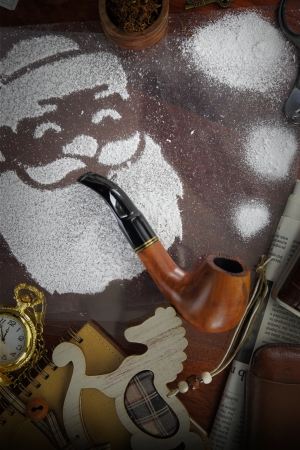 Santa made of snow spray smoking pipe on wooden desk photo