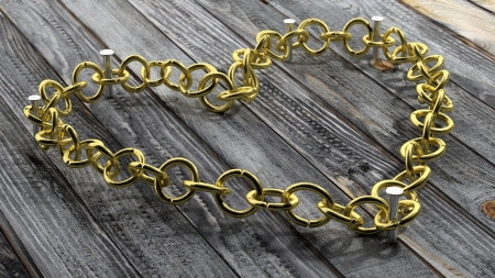 Golden chain in shape of heart, on wooden background photo