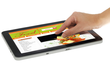 zooming: Hand zooming on tablet with recipe website template isolated Stock Photo