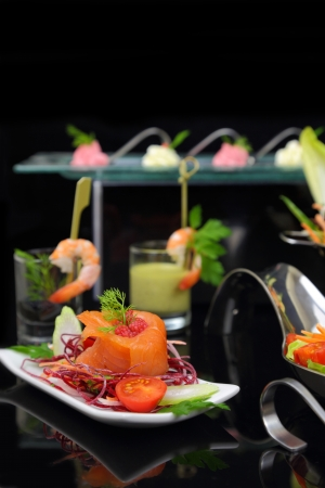 Smoked salmon with decoration and other dishes in background photo