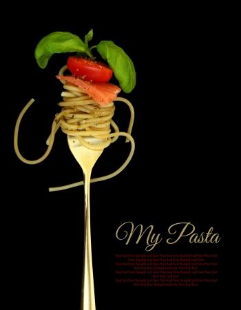 Fork with spaghetti, tomato, salmon and basil on black Stock Photo