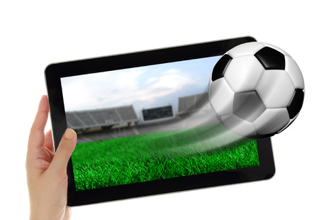 Hand holding tablet with soccer ball flying off screen  photo
