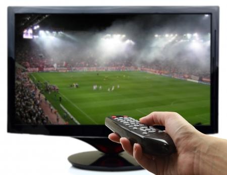 smart: Tv-scherm met een voetbalwedstrijd en hand met afstandsbediening