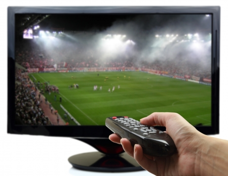 Tv screen with football match and hand with remote control photo