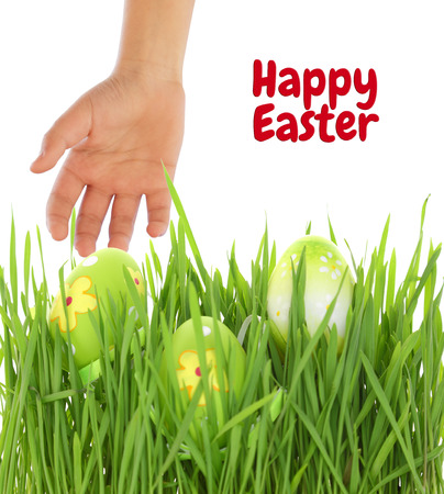 Hand reaching for Easter egg on green grass photo