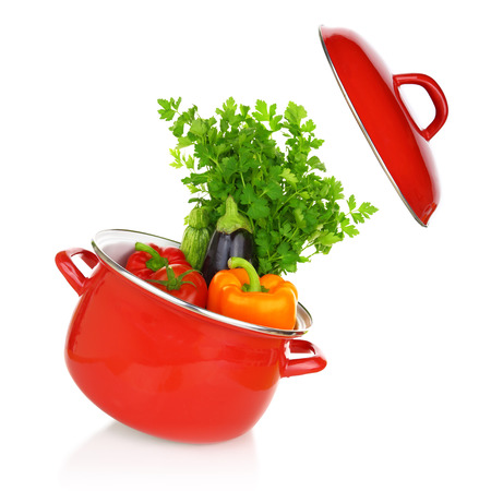 Colorful vegetables in a red cooking pot isolated on white background photo