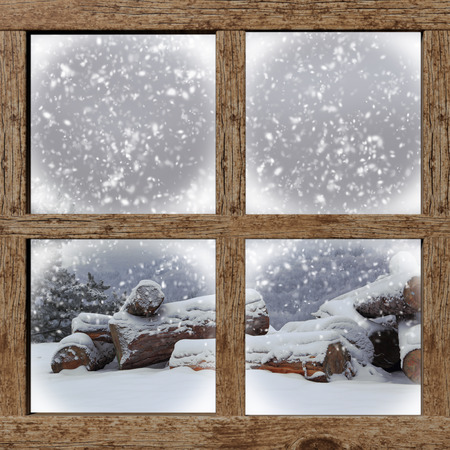 Winter outdoors view with firewood pile from wooden window photo
