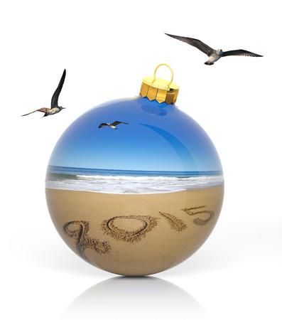 beach landscape: Christmas ball with 2015 written on sandy beach