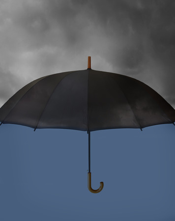 Umbrella with heavy clouds above and clear blue under photo