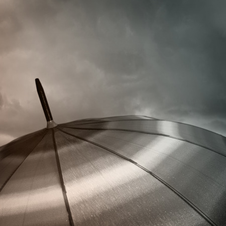 Umbrella top with raindrops and heavy clouds photo