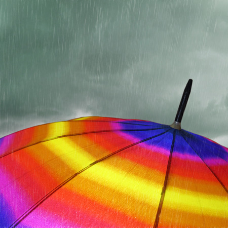 Colorful umbrella top with heavy rain and clouds photo