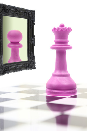 self respect: Queen looking in the mirror seeing pawn in reflection  Stock Photo