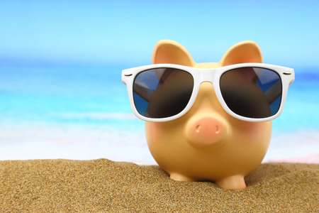 wealth: Summer piggy bank with sunglasses on the beach Stock Photo