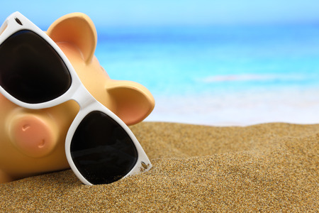 sales bank: Summer piggy bank with sunglasses on the beach Stock Photo