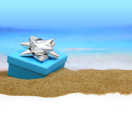 Gift box with ribbon on the sand photo
