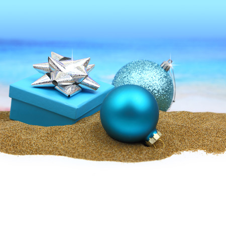 Gift box and Christmas balls on the sand photo