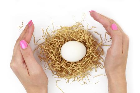 ovario: Las manos femeninas protegen huevo dentro del nido aislado en blanco