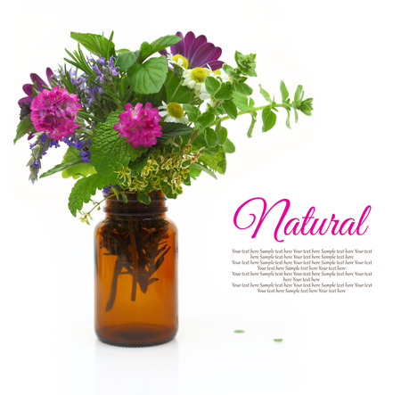 Fresh herbs and flowers in a medical bottle photo