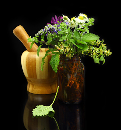 Mortar and pestle with fresh herbs and medical bottle photo