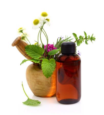 elixir: Mortero y majadero con hierbas frescas y una botella de aceite esencial
