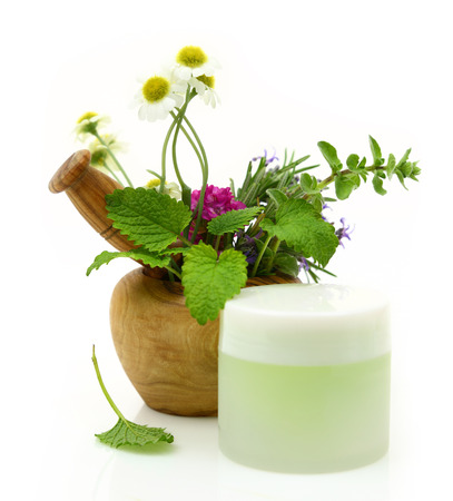 Wooden mortar with herbs and cosmetic cream photo