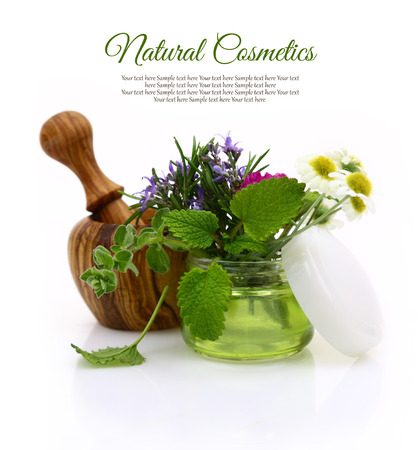 Wooden mortar and cosmetic cream jar with herbs inside photo