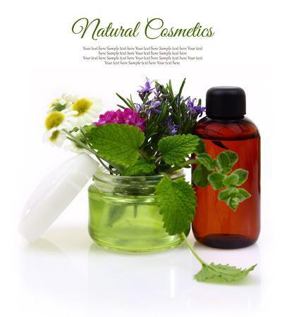 Cosmetic cream jar with herbs inside and essential oil bottle  photo