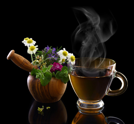 Cup of hot tea and mortar with fresh herbs photo