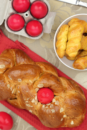 Easter sweet brioche with red eggs and vanilla cookies photo
