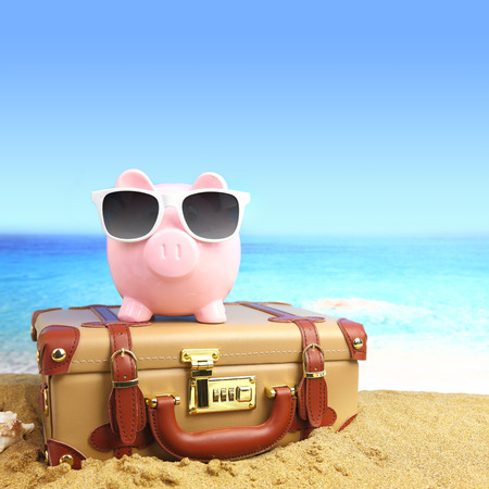 agencia de viajes: Maleta con la hucha con gafas de sol en la playa tropical Foto de archivo
