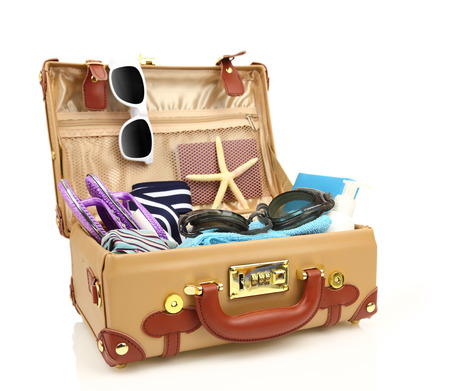 Ready to travel open suitcase with summer equipment isolated  photo