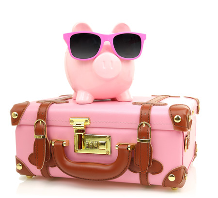 Pink suitcase with piggy bank in sunglasses isolated photo
